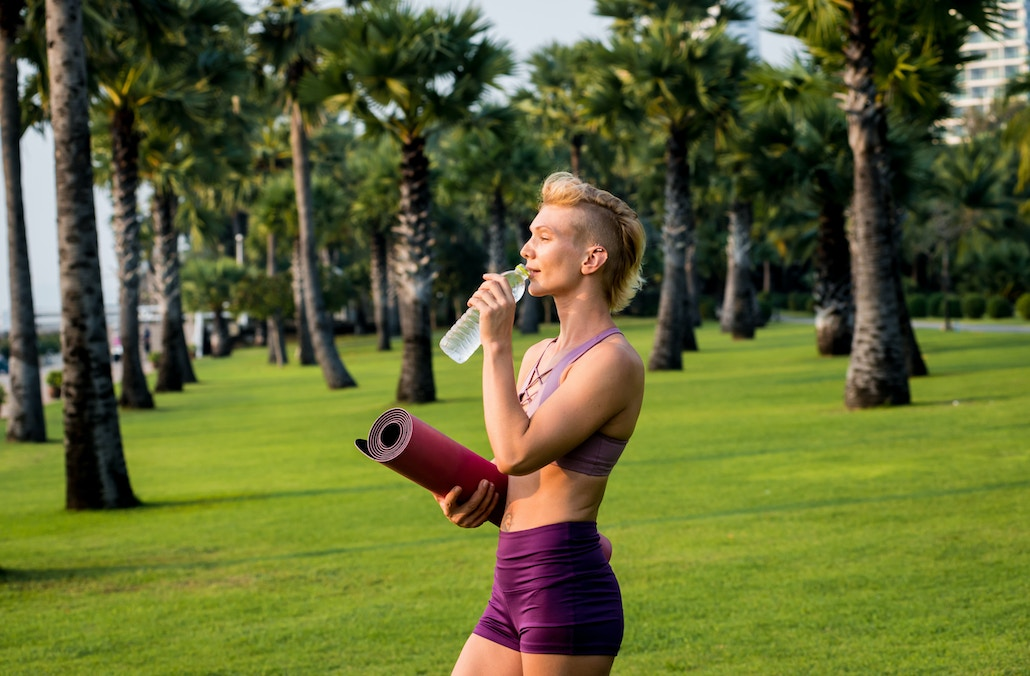 Sportive Woman Drinking Water to Hydrate Her Body